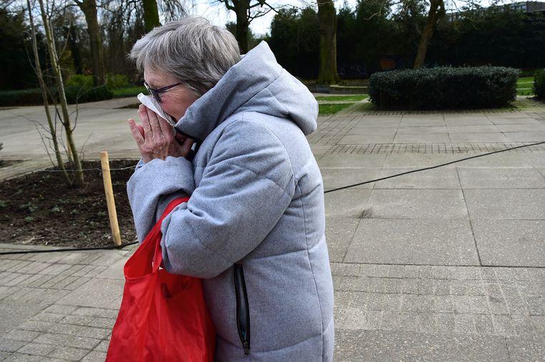 Een vrouw op straat snuit haar neus. Beeld Marcel van den Bergh / de Volkskrant