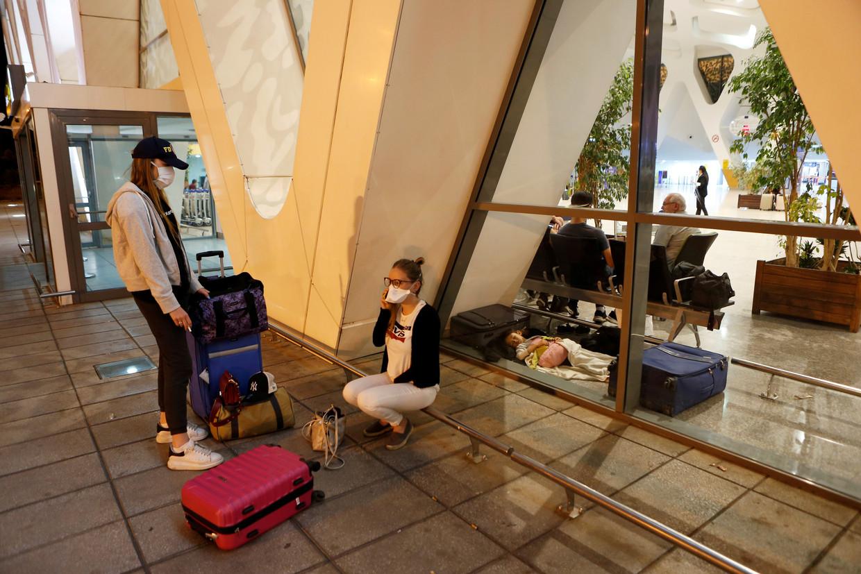 Toeristen wachten op het vliegveld van Marrakech in Marokko op repatriëring.  Beeld Reuters