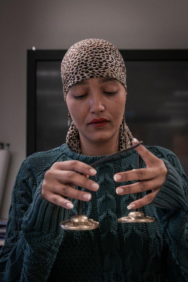 Fatima Boutaka begint de training met het luiden van Tingsha's, twee belletjes.  Beeld Dingena Mol
