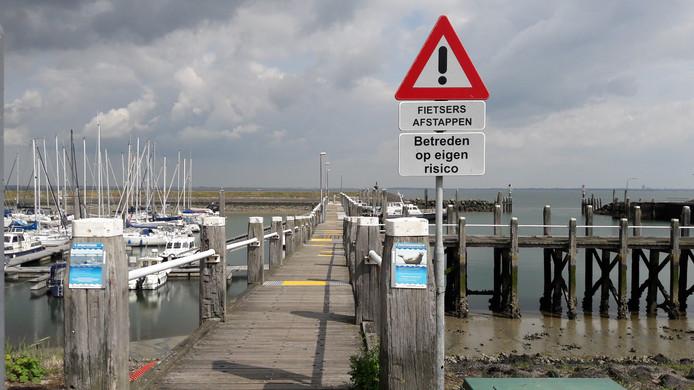 De versleten visserijsteiger in de haven van Colijnsplaat.