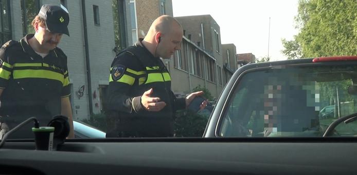De vermomde Goudse burgemeester Milo Schoenmaker (l) spreekt met een agent een automobilist aan, die zonder gordel rijdt.