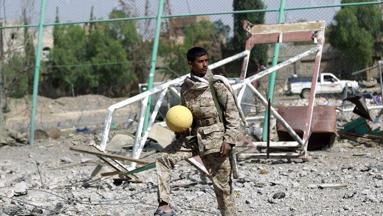 Een gewapende sjiitische Houthi in de hoofdstad Sanaa speelt voetbal in een decor van verwoestingen. Beeld AFP