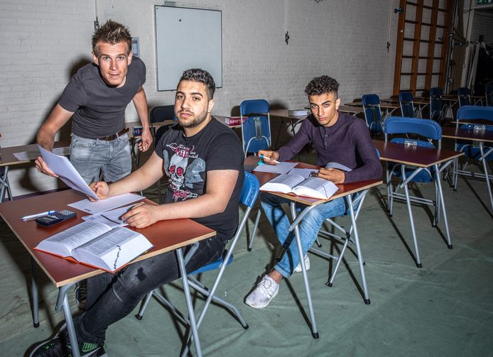 Walid Ghazzoula (voorgrond) en Ali Zein Alabedin in de examenzaal van de Van der Capellen scholengemeenschap, met onderwijscoördinator Thomas Bouter.
