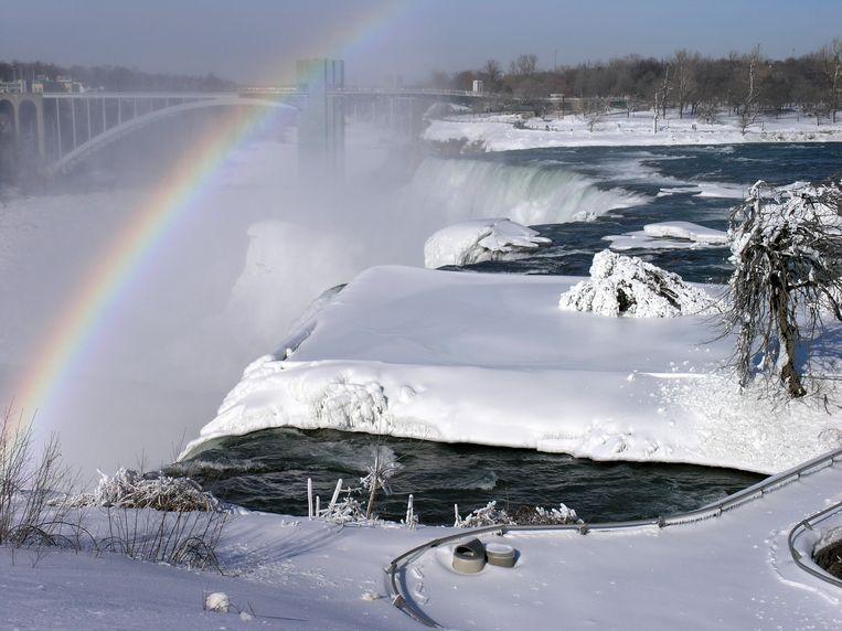 De Niagara Falls op de grens tussen Canada en Amerika zijn deels bevroren. En er komt zelfs een regenboog piepen.