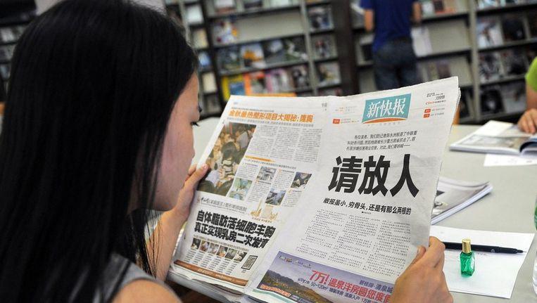 Vrouw leest een Chinese krant Beeld ANP