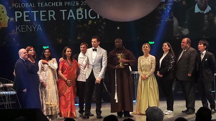 De winnaar Peter Tabichi is gekleed in een bruin gewaad, rechts naast hem staat Daisy.