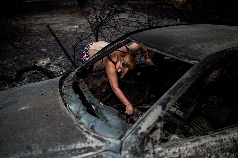 Een vrouw probeert tevergeefs persoonlijke bezittingen te vinden in haar uitgebrande auto.  Beeld AFP