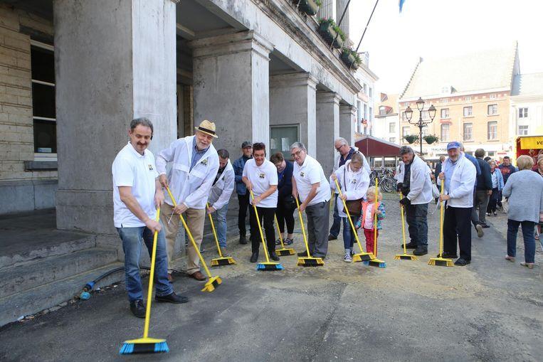 Enkele leden van Vlaams Belang vegen de straat voor het stadhuis.