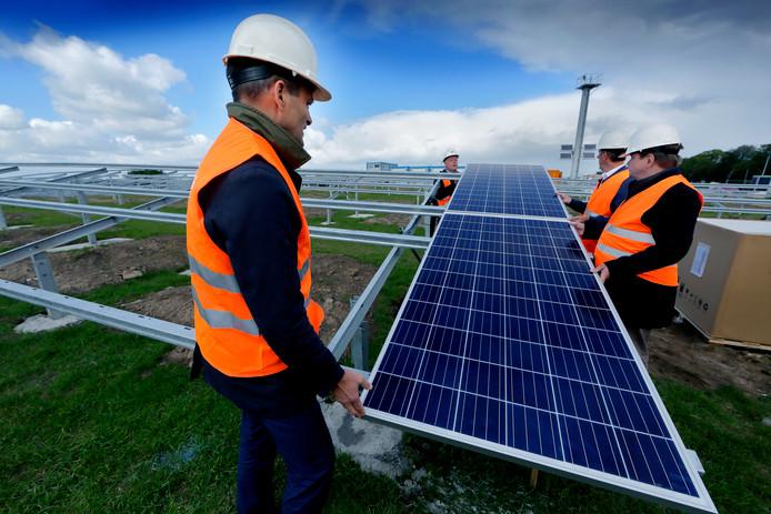 Wethouders Rik van der Linden en Maarten Burggraaf mochten afgelopen jaar de eerste zonnepanelen in de stellages schuiven op het zonnepark langs de Rijksstraatweg in Dordrecht.