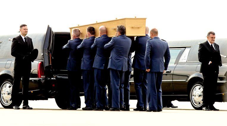 Een van de kisten met stoffelijke resten van slachtoffers van rampvlucht MH17 wordt naar een rouwwagen gedragen na aankomst op vliegbasis Eindhoven. Beeld null