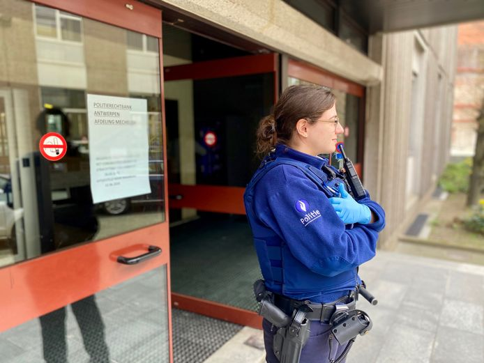 """Een agent van de Dienst Algemene Beveiliging (DAB) bewaakt de toegang van de rechtbank in Mechelen. """"Wie niet werd gedagvaard, komt er niet in"""""""