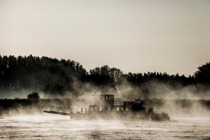 Het schaduwspel van het voetveer Aqua Ferro in het ochtendgloren op de Waal.