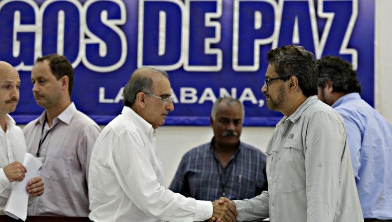 Onderhandelaars van de FARC en de regering schudden elkaar de hand. Beeld reuters