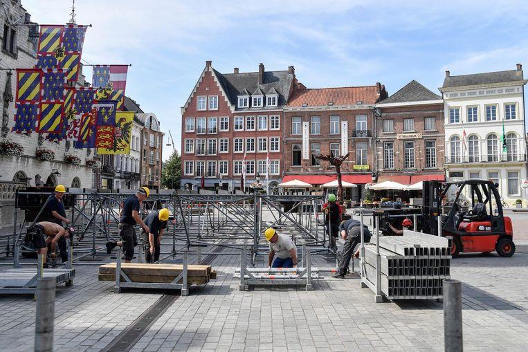 Op de Grote Markt zijn werklui in de weer om het centraal podium op te bouwen.
