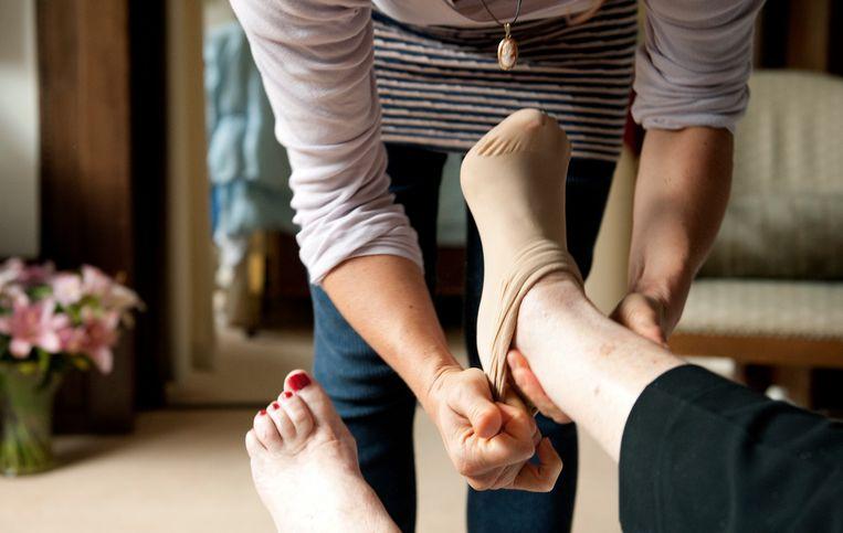 Een thuiszorgmedewerkster biedt hulp aan een oudere dame.  Beeld ANP XTRA