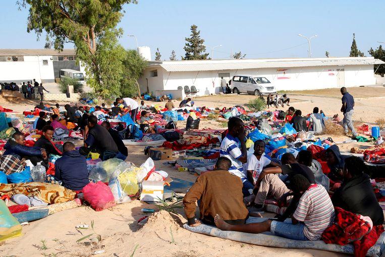 Migranten verbleven tijdelijk in de tuin van het gebombardeerde opvangcentrum.  Beeld REUTERS