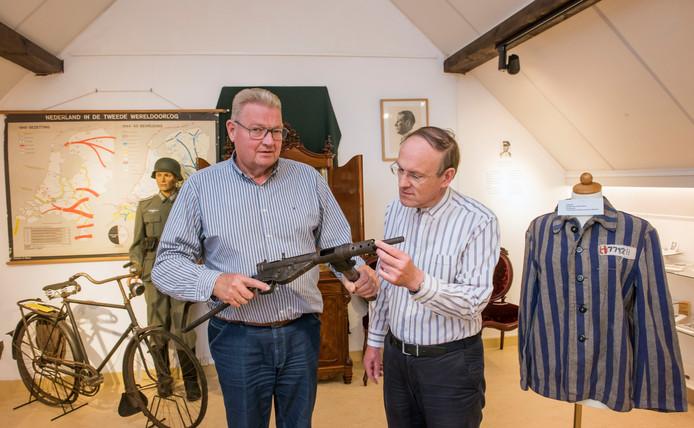 Henk van der Zwaag van museum De Tien Malen (l) en Jan van den Hoorn van Stichting Oktober'44 bestuderen in de tentoonstellingsruimte de stengun die werd gebruikt voor de aanslag op 30 september 1944 in Putten.