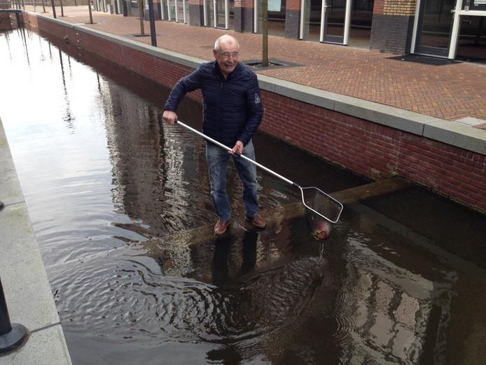 Hans van Maanen oefent alvast voor het uit de gracht vissen van de 80 goudvissen die hij er heeft uitgezet.