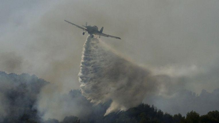 Een blusvliegtuig boven de brandende bossen van Mallorca. Beeld afp