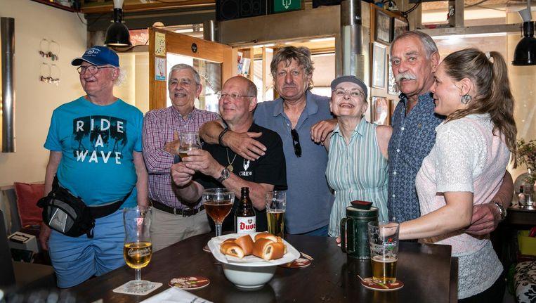 Vlnr (vergezeld door twee Amerikaanse toeristen met baseballpetten): veteranen Joost Lenz, Martin Maas, Cas Willems, Wil Janssen en barkeeper Saskia Smit. Beeld Dingena Mol
