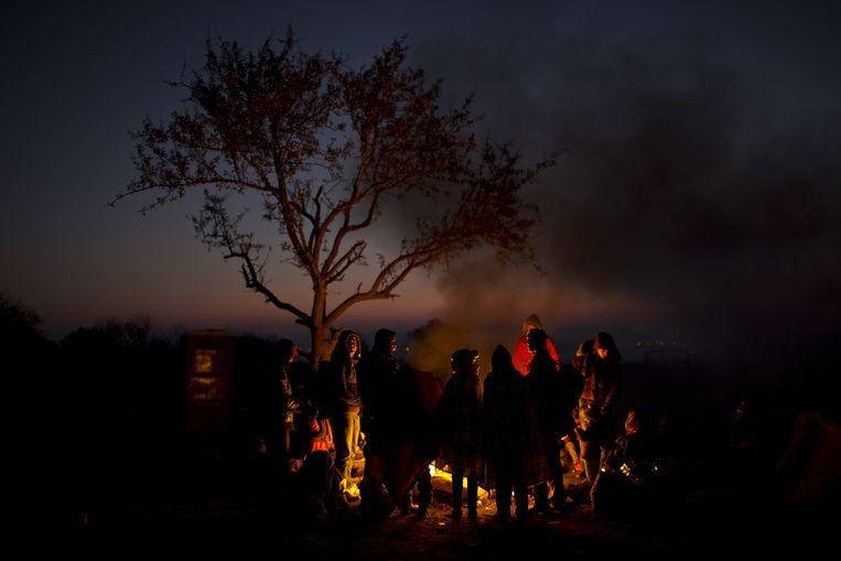 Vluchtelingen warmen zich aan het vuur in het Noord-Griekse idomeni. Beeld ap