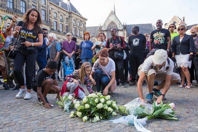 Bloemen worden neergelegd op de plek waar een taxichauffeur in 1983 weigerde de neergestoken en hevig bloedende Kerwin Duinmeijer mee te nemen. Beeld Maarten Brante