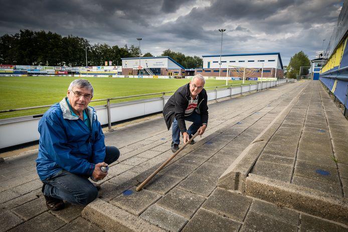Jan Vogelzang (links) en Jan Hof, lid van de toernooicommissie, meten met een stok de 1,5 meter afstand uit. Supporters zijn welkom bij wedstrijden, maar dan moeten ze wel op de blauwe stippen staan.