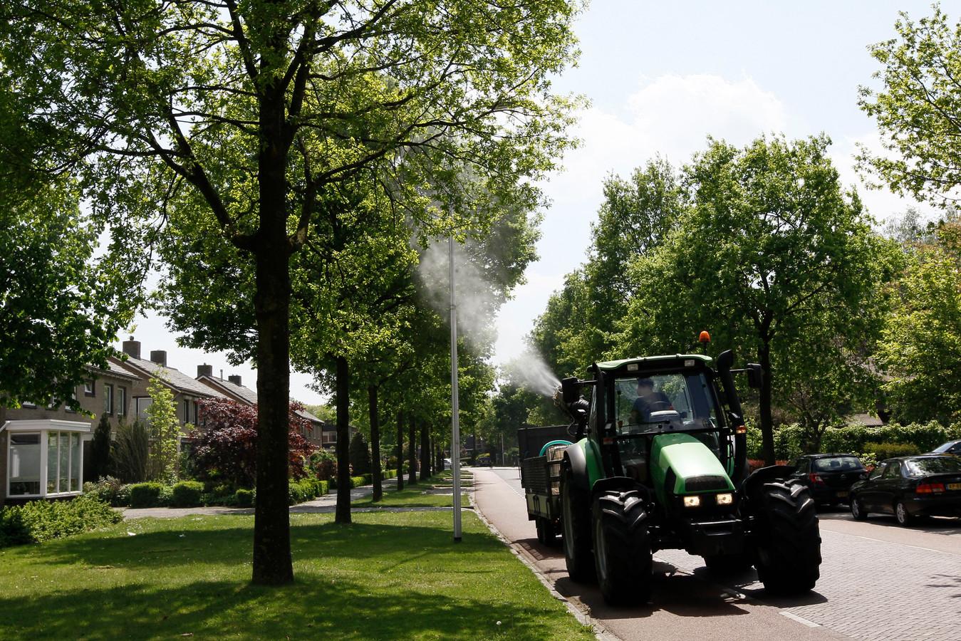Vanaf een aanhanger achter een tractor wordt in Raalte een wolk fijne druppeltjes van het biologische middel Xentari in boomkruinen gespoten. De gemeente Raalte schakelde daarvoor het Deventer bedrijf Pius Floris in.