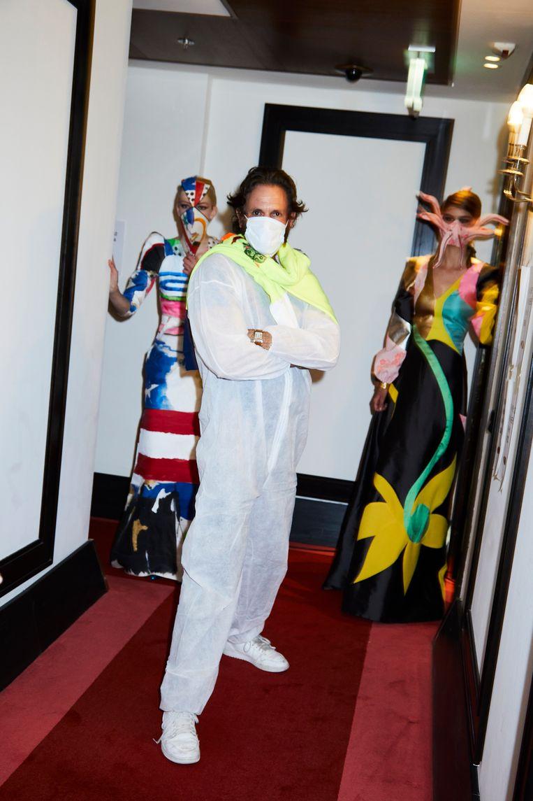 Couturier Ronald van der Kemp geflankeerd door modellen gekleed in door hem ontworpen jurken en mondmaskers. Beeld Marijke Aerden