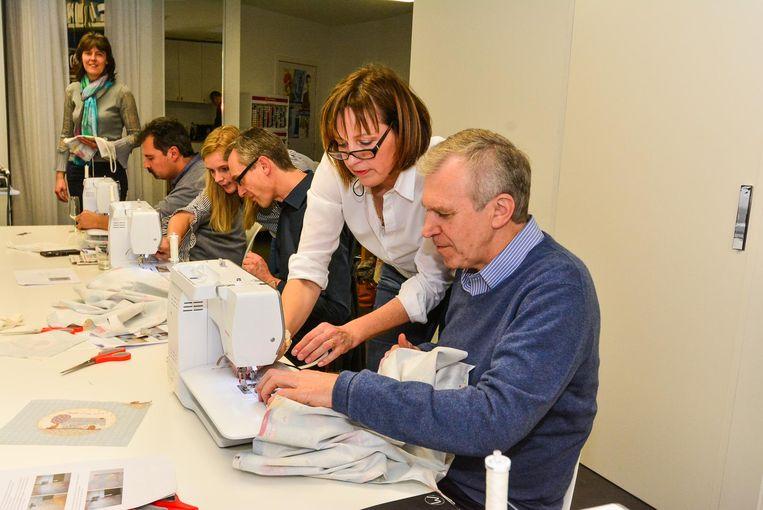 Yves Leterme en de andere mannen krijgen uitleg over hoe de naaimachines precies werken.