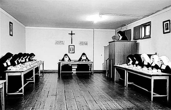 De zusters aan de sobere maaltijd in de refter van het klooster, rechts met witte kappen novicen.