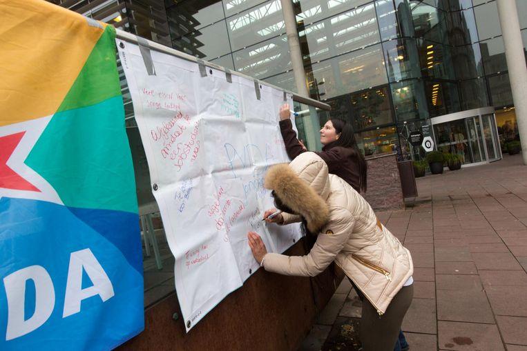 Op een doek op het stadsplein noteren jongeren de redenen waarom ze niet aan een job geraken.
