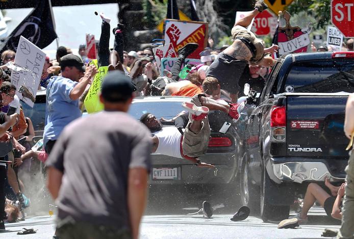 Een auto rijdt in op de demonstranten.