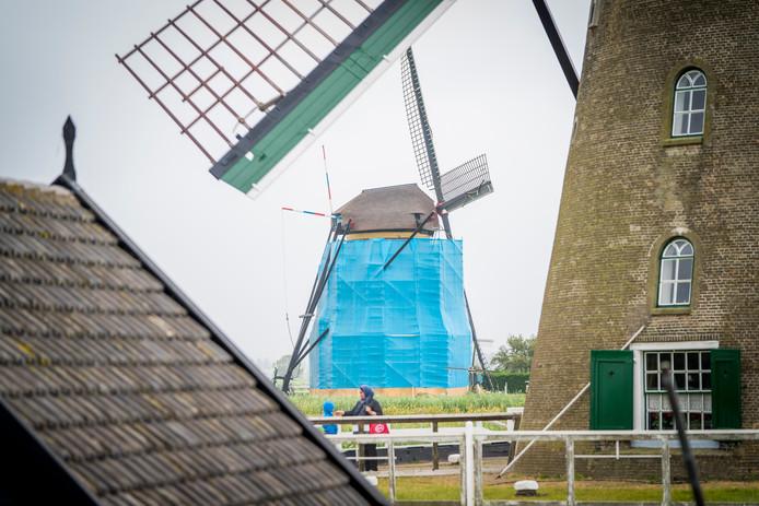 De ingepakte molen zorgt voor verbaasde blikken bij toeristen.