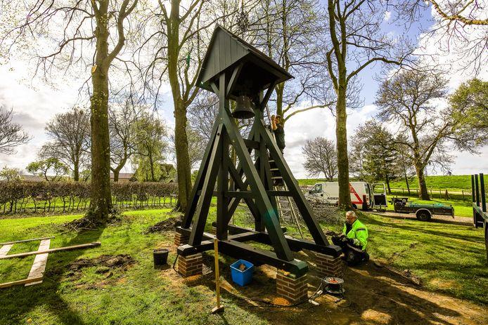 Berry Westerveen (op de ladder) en Eddie Groen (rechts) hebben de klokkenstoel, die jaren bij Aberson in opslag stond, op de begraafplaats in Baarlo geplaatst. Voortaan klinkt klokgelui bij begrafenissen.