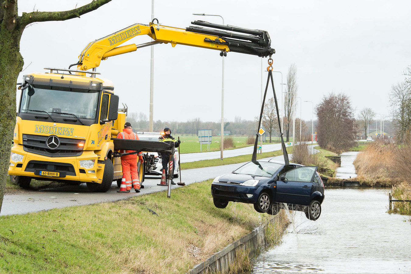 Een bergingbedrijf takelt de auto uit het water.