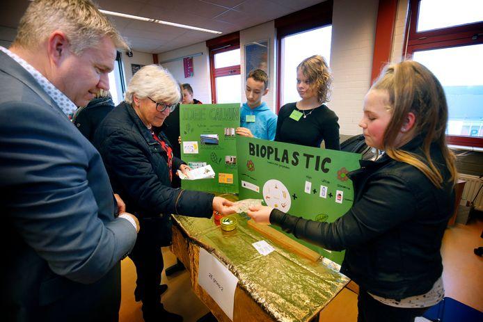 Leerlingen presenteren hun duurzame ideeën en prototypes aan belangstellenden. Wethouder Jan Nederveen kijkt toe.