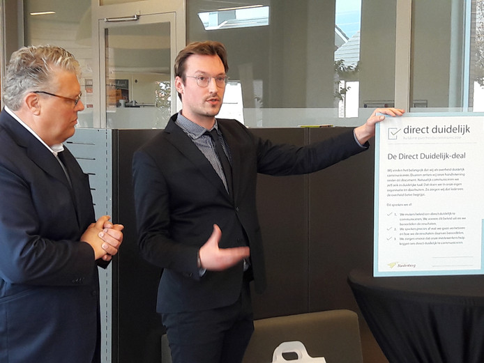 Wethouder Jan ten Kate (links) staat op het punt om de Direct Duidelijk-deal te ondertekenen. De 'brigadeleider' van het landelijke project geeft nog uitleg.