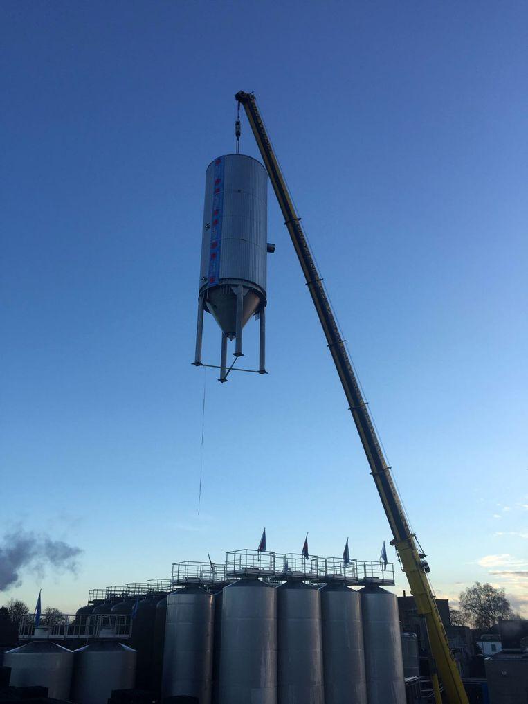 De tank wordt met grote kranen over de brouwerij getild.
