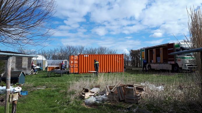 De 'illegale blokhut' (l) wordt door medewerkers van een verhuisbedrijf leeg gehaald terwijl agenten toekijken.