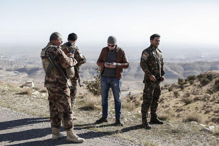 Remco Andersen spreekt met Koerdische Peshmerga terwijl hij wacht om Sinjar, Irak, binnen te gaan op 11 november 2015. Sinjar was een dag eerder ingenomen door IS. Beeld Sam Tarling