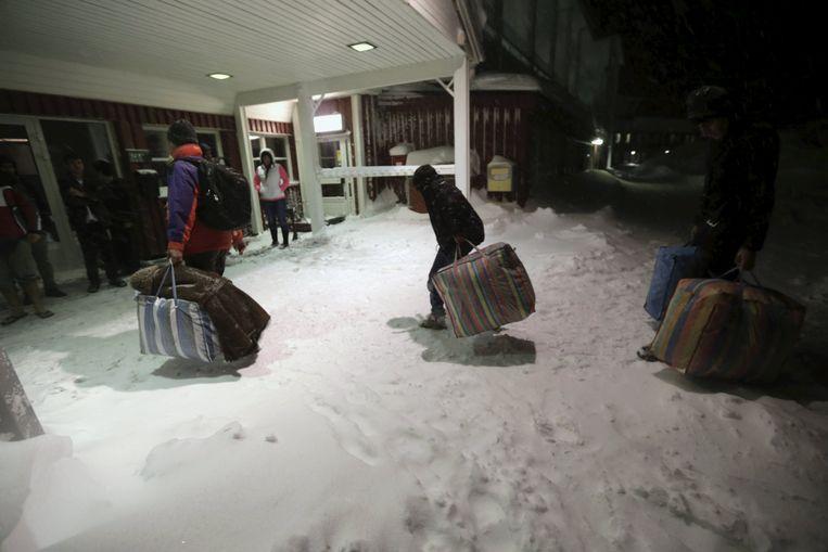 Vluchtelingen arriveren bij een hotel dat dienstdoet als opvanglocatie. Beeld REUTERS