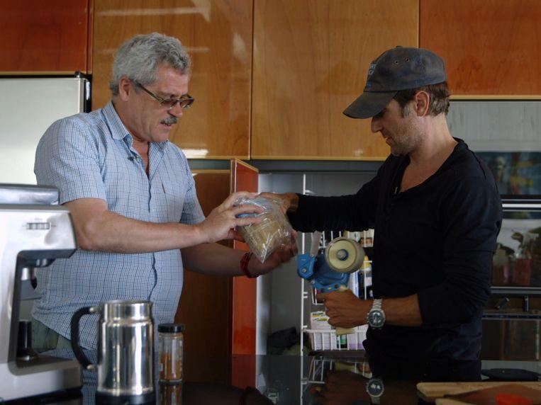 Grigori Rodtsjenkov (links), hier in actie met filmmaker Bryan Fogel, tijdens het inpakken van urinepotjes. Het beeld komt uit de documentaire 'Icarus'. Beeld Netflix