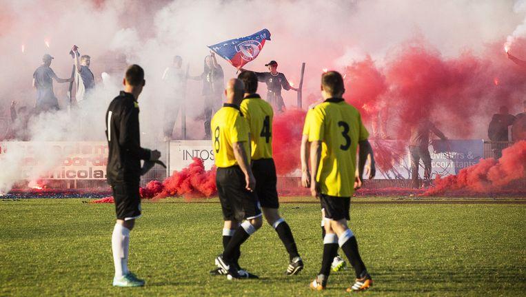 Spelers van Veendam kijken naar de rook veroorzaakt door fakkels van Haarlem-supporters. Beeld null