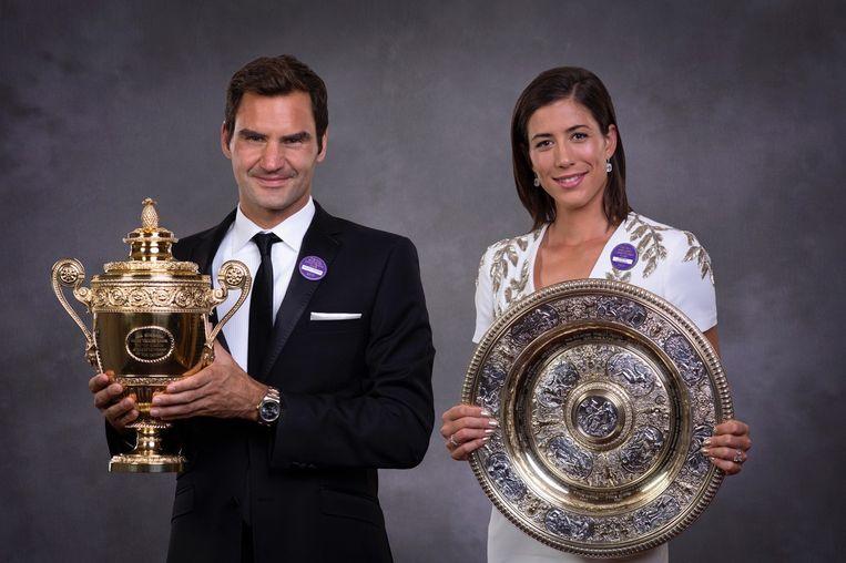 Roger Federer en Garbine Muguruza poseren met hun trofee tijdens het zogenaamde 'Winners Dinner'.