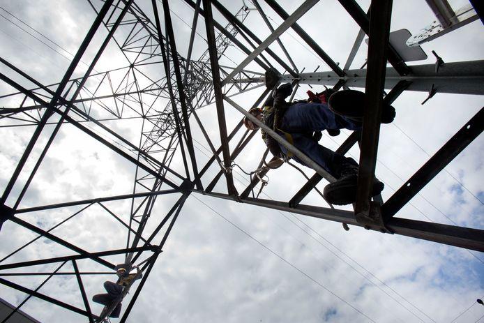 Werknemers van netbeheerder Tennet aan het werk in een mast aan de Veenendaalse Bobinestraat op archiefbeeld.