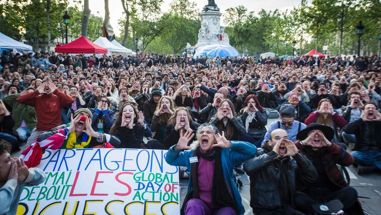 Aanhangers van 'Nuit Debout' schreeuwen op de Place de la République in Parijs. Beeld afp
