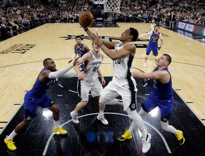 San Antonio Spurs guard DeMar DeRozan (m) is op weg naar de basket. Rechts Nikola Jokic, die ondanks 43 punten niet kon voorkomen dat Denver Nuggets onderuit ging.
