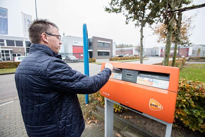 Ferry Theuws bij de brievenbus waar de facturen worden verstuurd