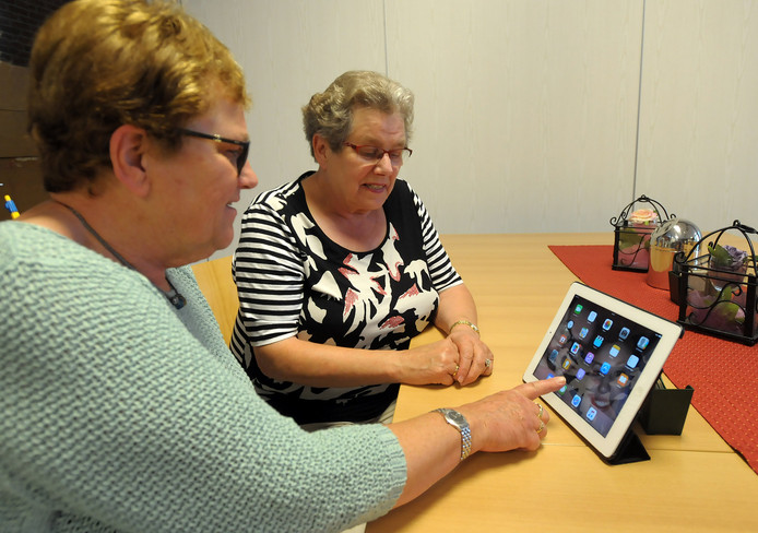 Vrijwilliger Jenny Burm praat Maria Broekaart bij over de mogelijkheden van een tablet.